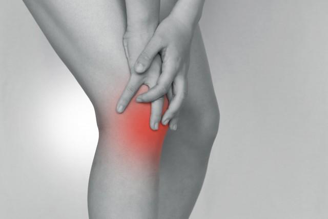 膝を抑える女性の写真